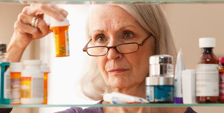 Image: Lady looking at prescription drugs in a medicine cabinet.