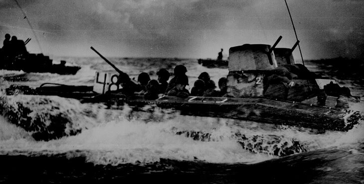 Marines ride on an amphibious vehicle near Guam July 1944. Photograph from the National Archives.