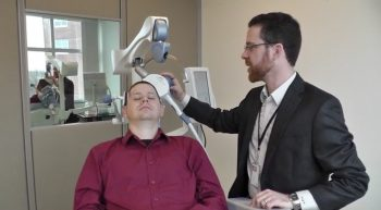 Dr. Noah Philip, Director of Psychiatric Neuromodulation at Providence VA, treats a patient using TMS therapy.