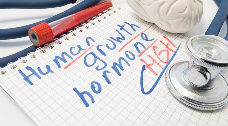 Note inscribed with Human Growth Hormone (HGH) or Somatotropin is surrounded by laboratory test tube with blood, brain figure and stethoscope. Significance and effects of growth hormone on human body