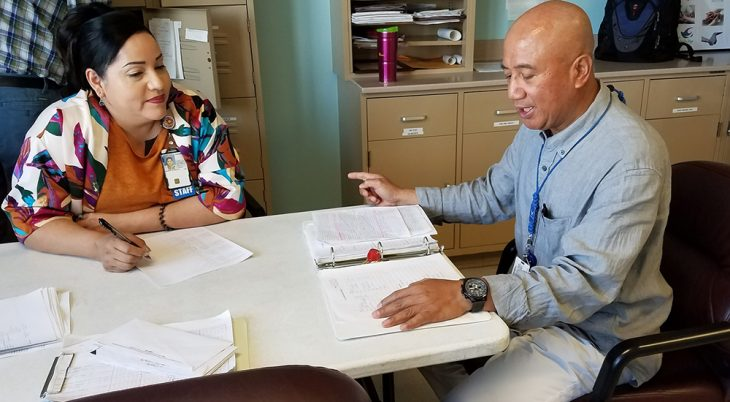 Manuel Martin discusses patient conditions with another nurse at morning report