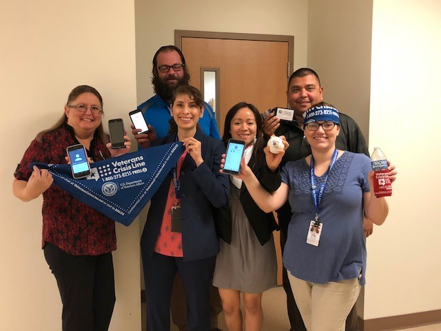 Members of the VA Texa Valley Coastal Bend Health Care System Call Center, also known as the VCB Call Center, show that they have completed the VCL Challenge by holding up their phones to show that they've added the Veterans Crisis Line number to their contacts list on July 20, 2018. Shown in photo are (first row) Connie Flores, Raquel Nava, Anaia Funtanilla, and Traci Hoekema;(second row) Martin Chase and Edward Moreno. You too can complete the VCL Challenge and add Veterans Crisis Line number 1-800-273-8255 and Press 1 to your contacts list. It could save your life or the life of a Veteran you may know. (U.S. Department of Veterans Affairs photo by Cecilia Garza-Garcia)