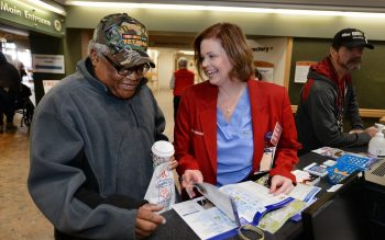 Veteran Albert Summons gets help from Central Arkansas VA Red Coat Ambassador Kim Womack, a surgical nurse. (photo by Jeff Bowen.)