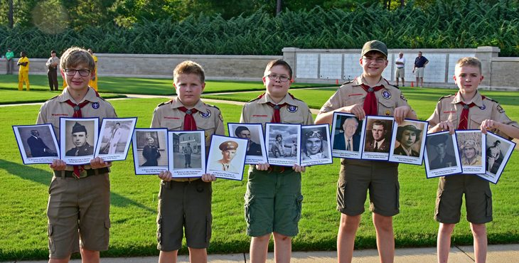 Five young boy scouts holding pictures of Veterans in front of a open grass field.