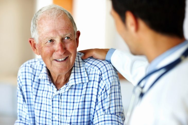 Photo shows a healthcare worker and an elderly patient.