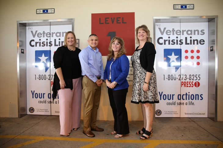 September 6, 2018 – Members of VA Texas Valley Coastal Bend Health Care System Mental Health pose for group photo in front of the elevator doors on the first floor of the parking garage of the VA Health Care Center at Harlingen, Texas, which now display the logo and number of the Veterans Crisis Line.  (U.S. Department of Veterans Affairs photo by Luis H. Loza Gutierrez)
