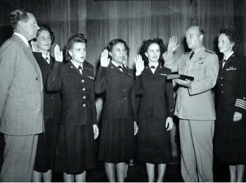 Rear Admiral George L. Russell, USN, (Judge Advocate General of the Navy) Swears in the first six women in the Regular Navy while the Secretary of the Navy John L. Sullivan, far left, looks on. Captain Joy B. Hancock, Director of the Womans Reserve, is next to RADM Russell, July 7, 1948. The first six enlisted women are: Front row: (left to right) Chief Yeoman Wilma J. Marchal, USN; Yeoman Second Class Edna E. Young, USN; Hospital Corpsman First Class Ruth Flora, USN. Second row: (left to right) Aviation Storekeeper First Class Kay L. Langen, USN; (hidden behind the front row): Storekeeper Second Class Frances T. Devaney, USN; and Teleman Doris R. Robertson, USN. Photo courtesy of NHHC.