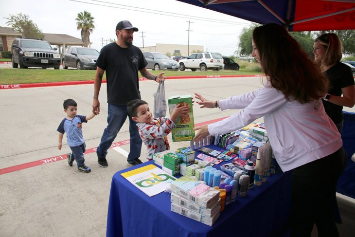 (Far right) Gina Guell smiles as fellow military spouse and volunteer, Lisa Quirk, reaches out to accept a large box of granola bars being donated by four-year-old Ivan Hernandez and his family, during the Boots & Badges care package drive held October 26, 2018, at Vet Center in Laredo, Texas. Local resident and businessman Hector Hernandez said he brought his sons Ivan and Jack [age 2] in order to set a good example for his children from an early age about the importance of supporting our nation's Veterans and giving back to your community.