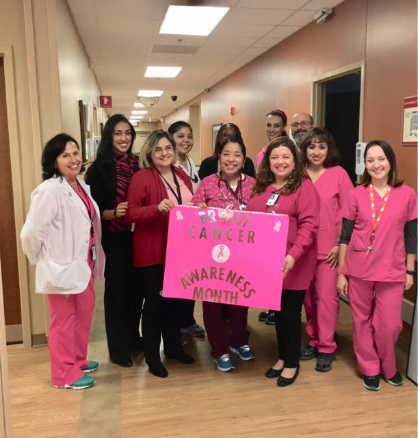 With a large pink banner at front and center VA employees at the VA outpatient clinic in Laredo, Texas, pose for a group photo on October 17, 2018, while wearing different pink garments in order to help support Breast Cancer Awareness Month. (Photo courtesy of Crystal Cabido)