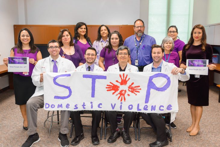 With colorful banners and signs in some of their hands, staff members at the Harlingen VA Outpatient Clinic pose for a group photo while wearing various purple garments on October 10, 2018. The staff wore purple during the month of October in observance of this year's Domestic Violence Awareness Month. (U.S. Department of Veterans Affairs photo by Abel Flores)