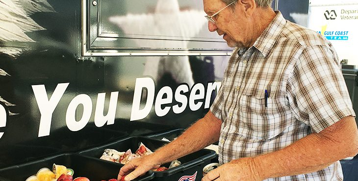 Picture of an elderly man reaching out to grab food.