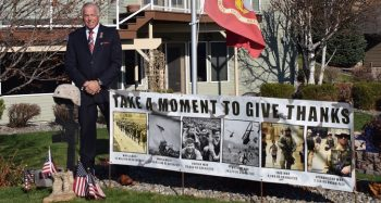 IMAGE: Richard Shutts with a banner outside of his home