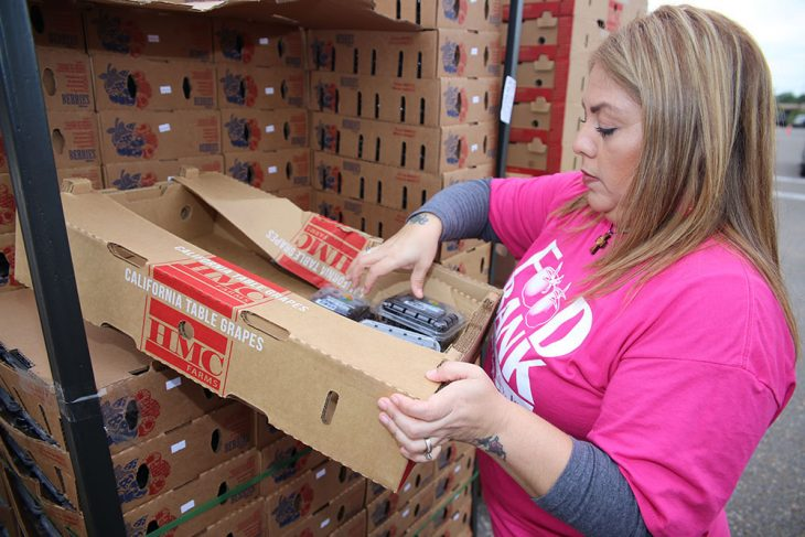 Food Bank of the Rio Grande Valley food sourcing specialist, Rachel Mendoza, places a few containers of black berries during the Free Produce Distribution Drive-thru held December 12, 2018, at the parking lot of the VA outpatient clinic at McAllen, Texas. (U.S. Department of Veterans Affairs photo by Luis H. Loza Gutierrez)