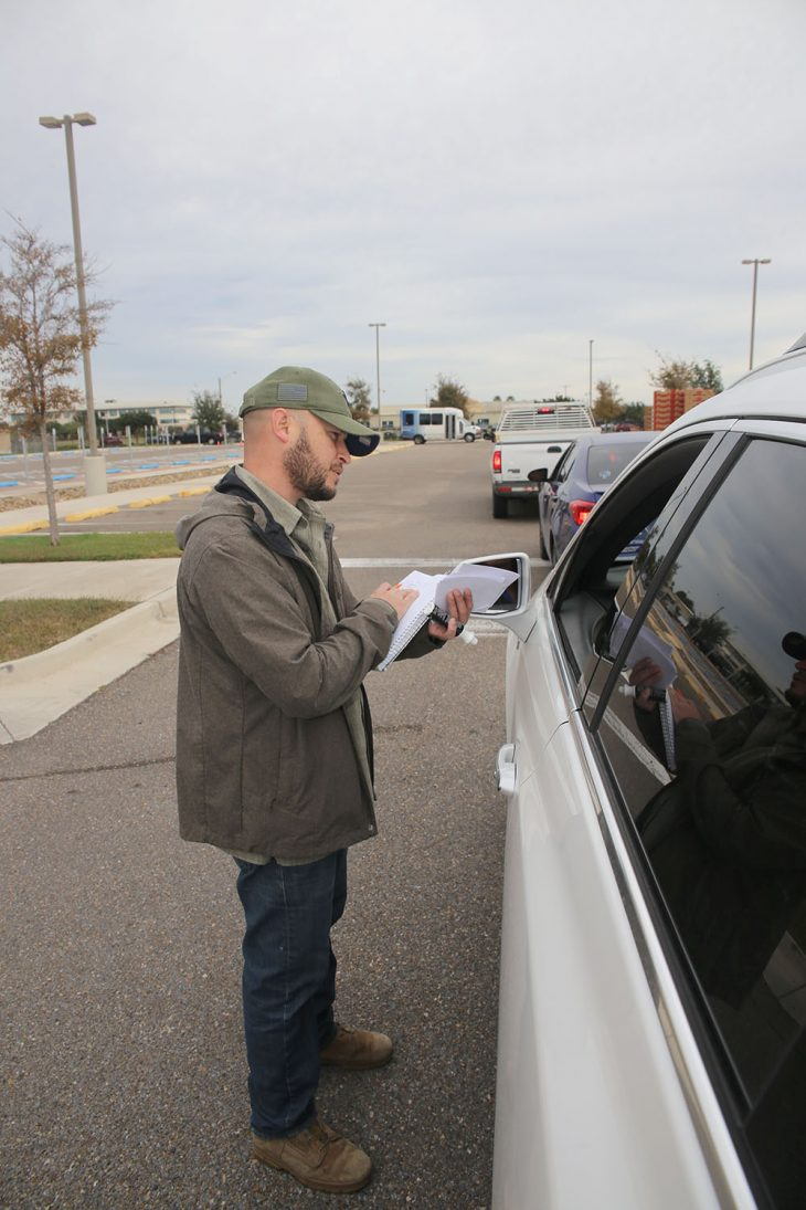 Food Bank of the Rio Grande Valley project manager, Miguel Del Bosque, verifies the Veteran status of a donation recipient during the Free Produce Distribution Drive-thru held December 12, 2018, at the parking lot of the VA outpatient clinic at McAllen, Texas. (U.S. Department of Veterans Affairs photo by Luis H. Loza Gutierrez)
