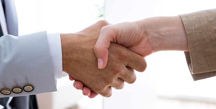 Image shows two people shaking hands