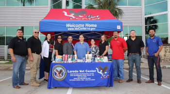 Eleven people standing at a table in front of a Vet Center