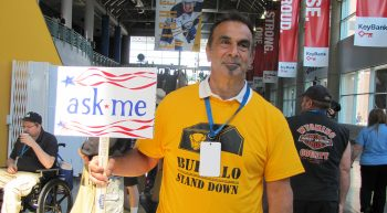 Man holding a ASK ME sign at a Stand Down