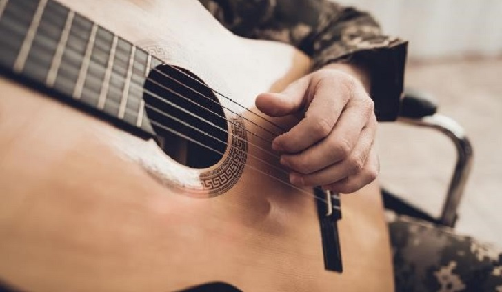 IMAGE: Hand strumming a guitar
