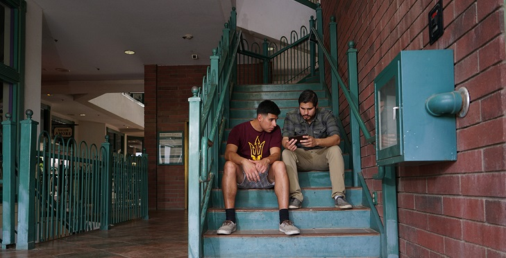 IMAGE: Two men sitting on the stairs.