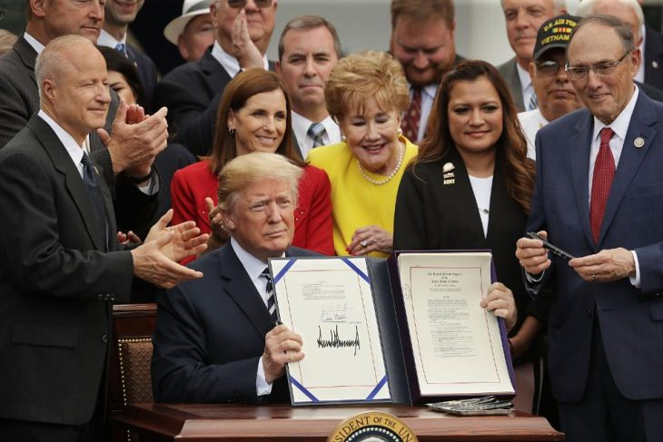 Picture shows president Donald Trump holding up a signed copy of the MISSION Act