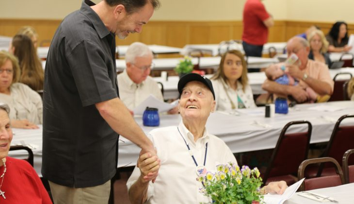 Mike Hagen, fellow Veteran and friend shakes hands with Bill at a recognition ceremony.