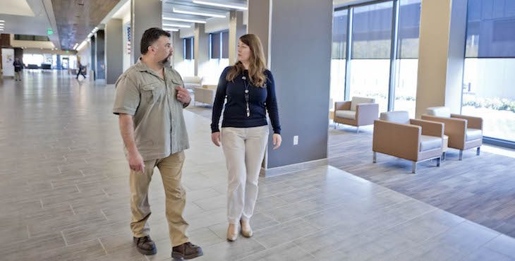 A Picture of two people walking in a hospital