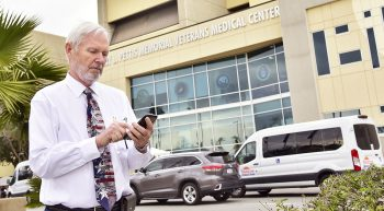 A man checking his mobile phone in front of a VA Medical Center