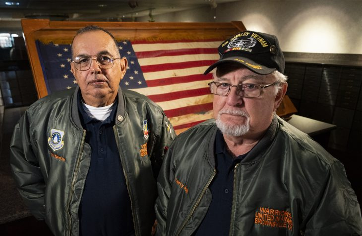 PORTRAIT of Tony Garcia and Larry Jokl in front of the ceremonial flag