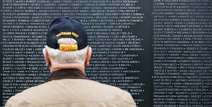 A veteran stands in front of the Wall that Heals