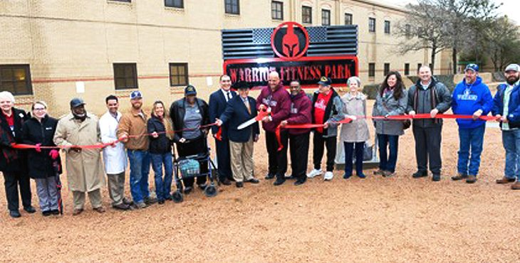 Picture of multiple people holding a ribbon during a ribbon cutting event at a new fitness park