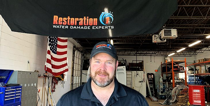 Graphic for Restoration 1 - shows man looking at camera in a garage with a banner for Restoration 1 hanging overhead.
