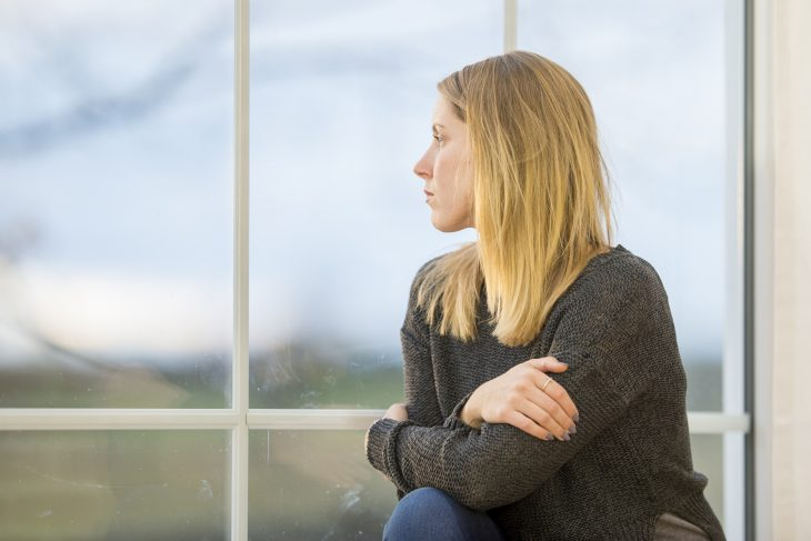 IMAGE of woman sitting at home by a window