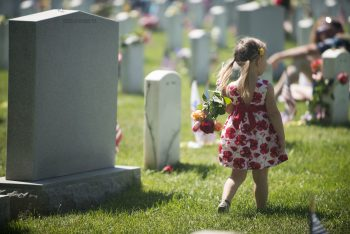 Image of child walking with flowers during Memorial Day