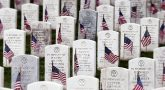Picture of a graveyard with tombstones decorated with American flags