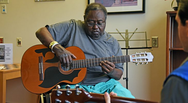 A man learning to play the guitar
