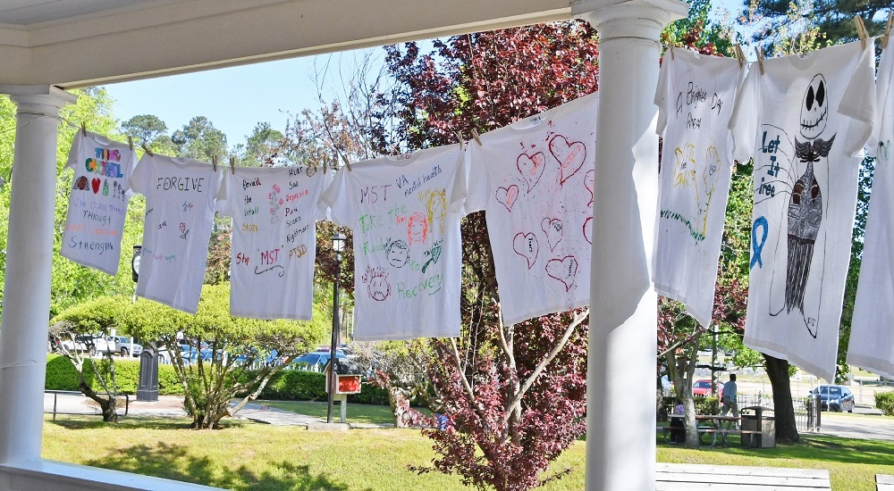 A row of tee shirts bearing slogans that reference military sexual trauma hanging on a clothesline