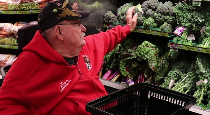 A male Veteran in a red sweatshirt reaches to place broccoli in a shopping cart in a supermarket