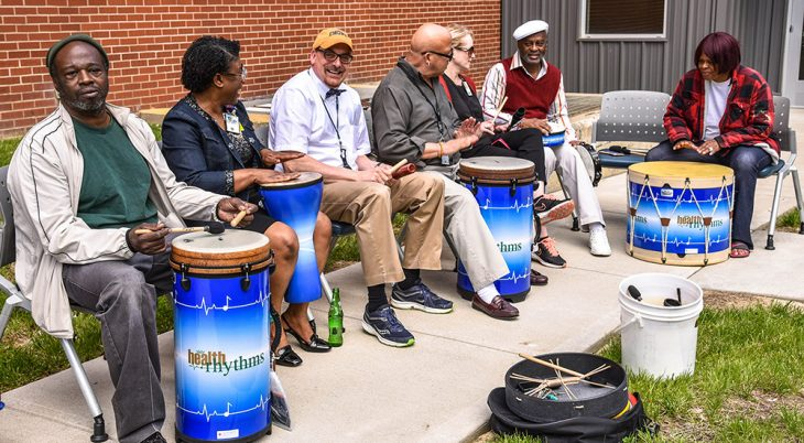 Men and women sitting in chairs with drums outside.