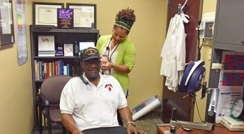 Clinician fits a male Veteran with a hearing aid fitting collar