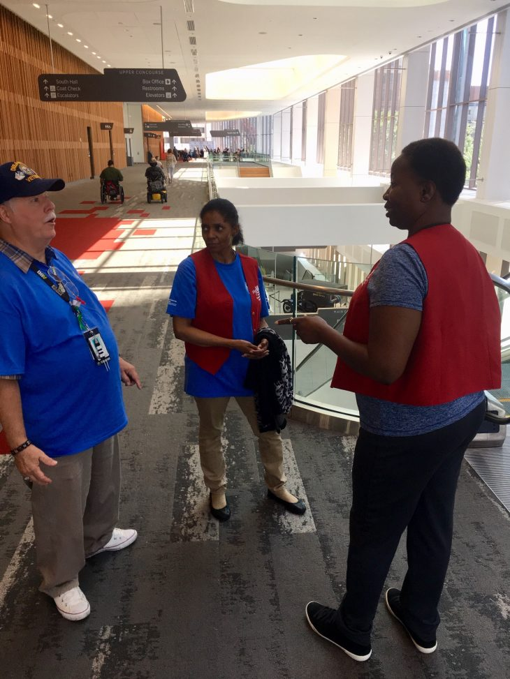 Two of the Red Coat volunteers speak with a Veteran about way finding and the events schedule at the wheelchair games.