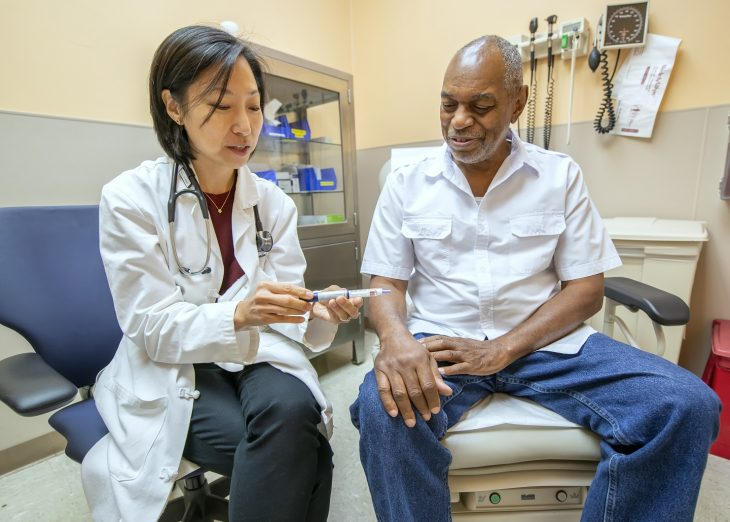 A doctor in a white coat shows an insulin pen to a patient.