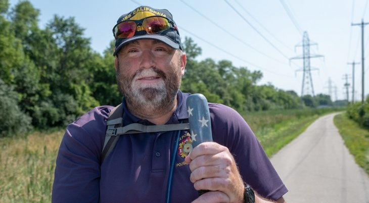 A man with a hiking staff on a walking trail