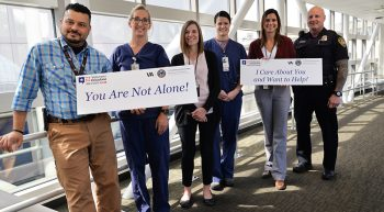 Six men and women standing in a hallway holding suicide prevention message signs.