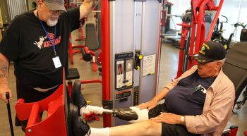 One man stands next to a piece of gym equipment while another man, who has a prosthetic leg, does leg presses.