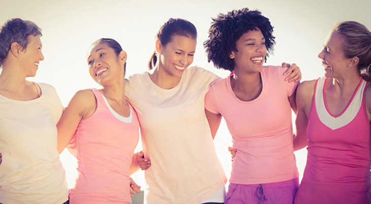 Five young women arm in arm, wearing pink to celebrate breast cancer awareness
