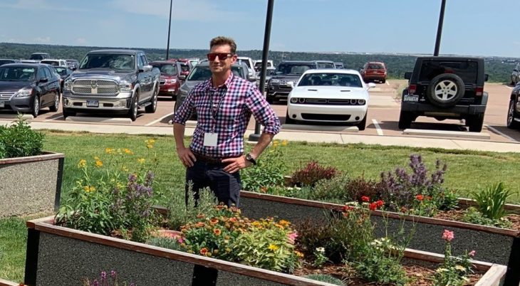 A man standing next to raised planting beds planted with flowers