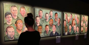 Patron looks at Portraits of Courage paintings