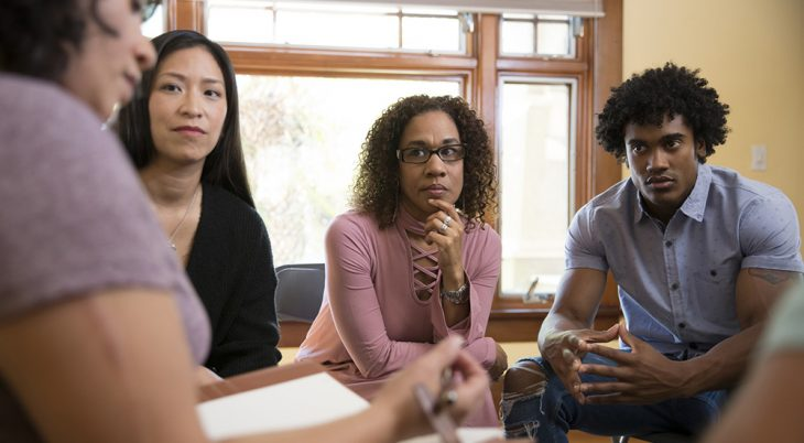 Three people listen to a female counselor in an office