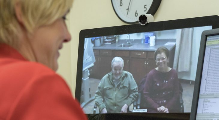 A doctor at a desk with a patient and the patient's wife visible on the doctor's computer screen