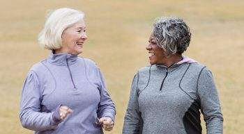 Two women wearing workout gear, smiling and talking